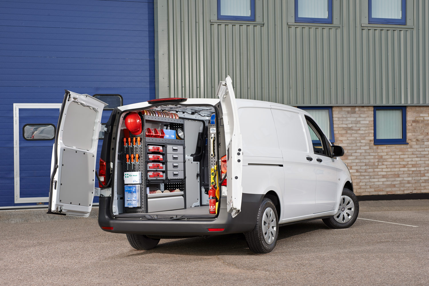 Van fitted out with modul-system van racking parked next to a warehouse